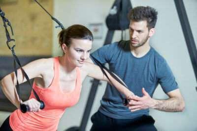 Couple in fitness studio at suspension training