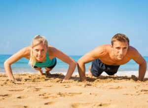Couple doing push ups on the beach