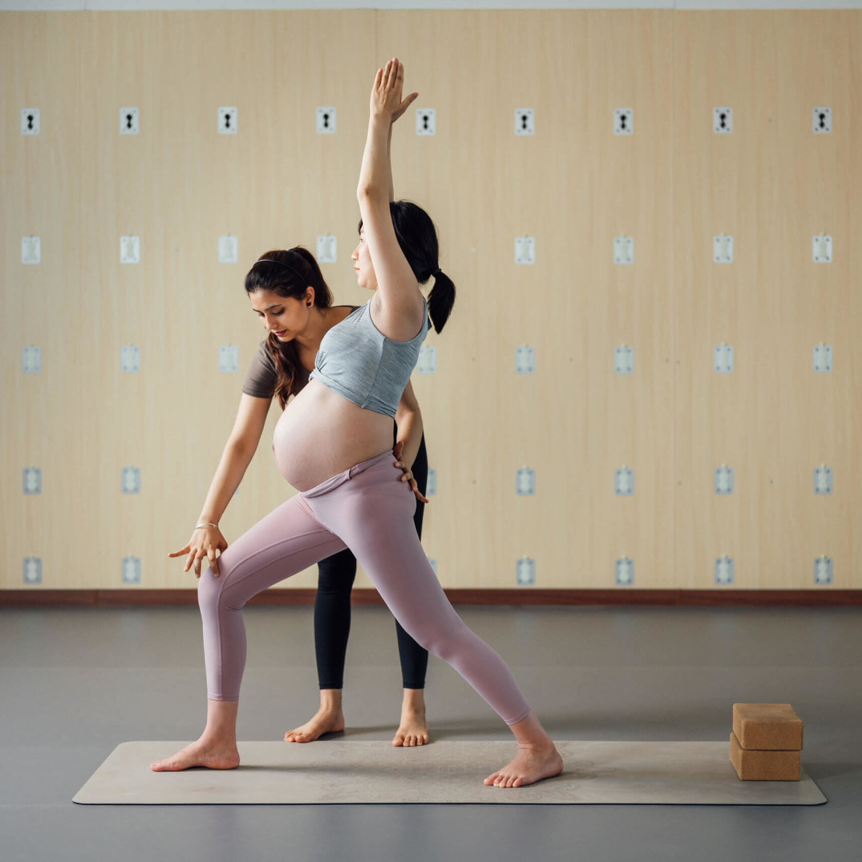 Pregnant woman doing yoga with the instruction of trainer in studio
